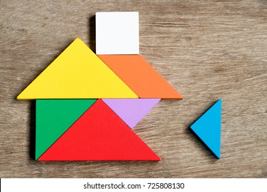 Colorful tangram puzzle in home shape wait for fulfill on wood background (Concept for build dream house, happy family life, property investment)
