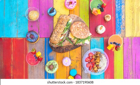Colorful and tasty drinks and snacks with smoothies, cupcakes, donuts and sandwiches on a colorful wood table