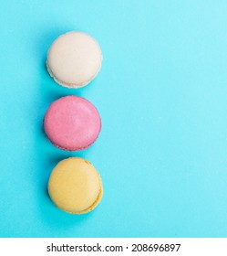 Colorful and tasty  French Macarons on blue background.Top view.