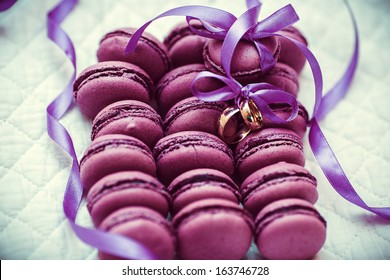 Colorful and tasty purple Macaroons on white with wedding rings
