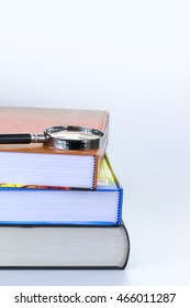Colorful textbooks and magnifying glass isolated on white with right copy-space.