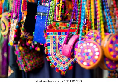 Colorful textile hand bags or purses of various shapes hanging in a store against a blurred background. Shot in a shop in the handicraft market in Ahmedabad, gujarat, india, asia. The very colorful
