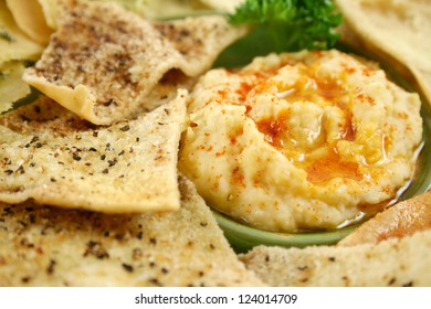 Colorful and textured baked pita bread crisps with hommus dip.