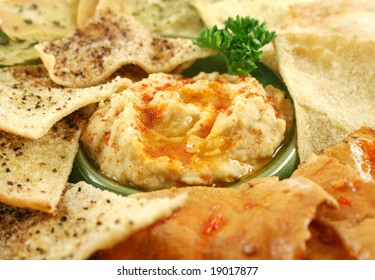 Colorful and textured baked pita bread crisps with hummus dip.