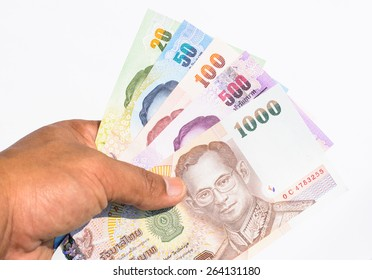 Colorful of Thai currency,banknotes in a hand with white background looking forward to business and investing in Thailand