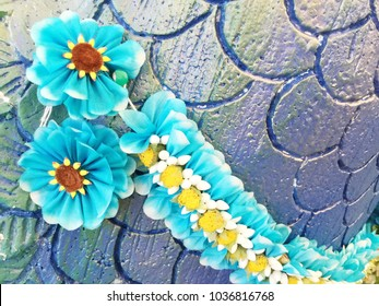 Colorful thai garland on the foam carved multicolored feathers wall.