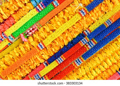 Colorful Thai garland, traditional flower decor, national ornament, Thailand, multicolor  texture from garlands, symbol of Asia, asian background, yellow, red, blue and green colours, color decoration