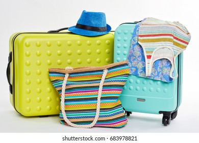 Colorful things for summer recreation. Suitcases, clothes, hat, handbag.