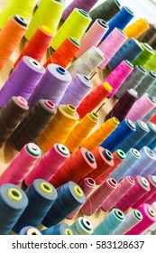 Colorful thread spools used in fabric and textile industry. The concept of sewing production.