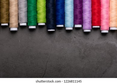 Colorful threads on grey background, flat lay with copy space