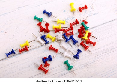 Colorful Thumbtack on white wooden background. Set of multicoloured Thumb Pins also called Push Pins which is used to pin notes to the notice board.