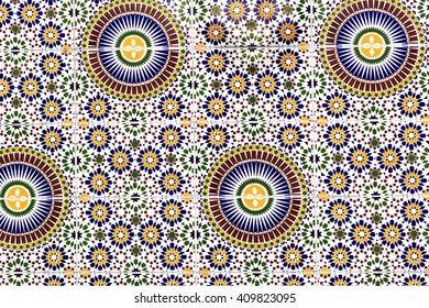 Colorful tile pattern (zellige) from the wall of ancient building in Marrakech, Morocco. Zellige is terra cotta tilework covered with enamel in the form of chips set into plaster.