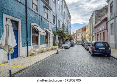 Colorful tiled buildings and narrow cobblestone street with parked cars and street side dining in Lisbon, Portugal