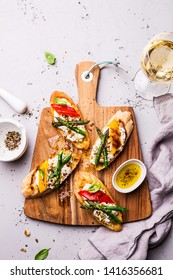Colorful toasts (sandwiches) with cottage cheese, grilled pepper and asparagus on wooden chopping board. Meal captured from above (top view, flat lay), gray stone background. Free copy (text) space.