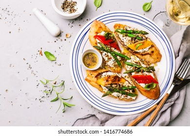 Colorful toasts (sandwiches) with cottage cheese, grilled pepper and asparagus on the white plate. Meal captured from above (top view, flat lay), gray stone background. Free copy (text) space.