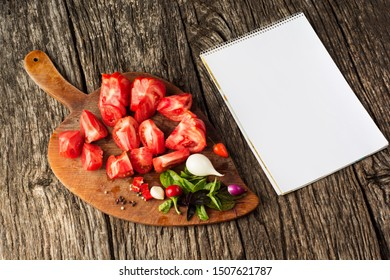 Colorful Tomatoes Background. Fresh Organic Tomatoes on kitchen board with blank notebook on vintage rustic background.