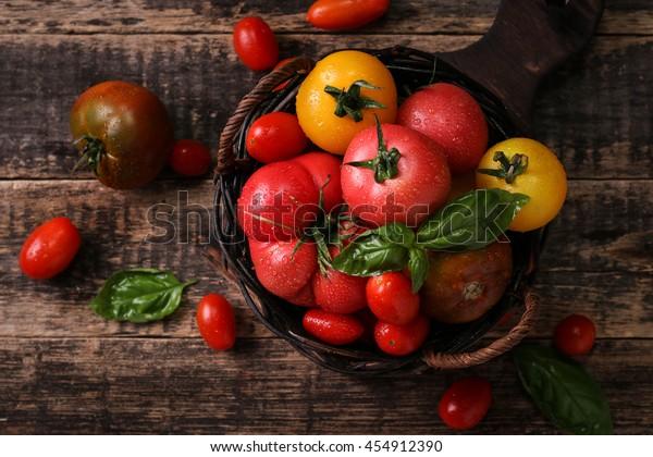 Pomodori colorati, rosso, giallo, arancione, verde su sfondo di legno vintage