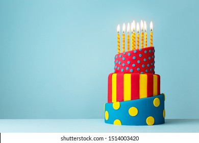 Colorful topsy turvy birthday cake with candles - Shutterstock ID 1514003420