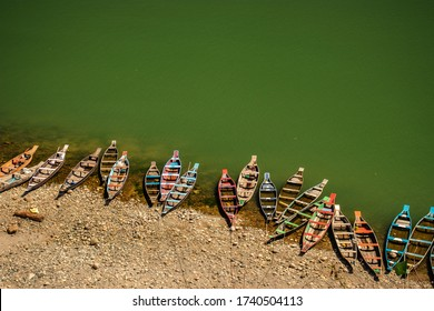 colorful tourist traditional wood boats isolated many at river edge image is taken at dwaki lake meghalya india. it is showing the pristine beauty of north east india.