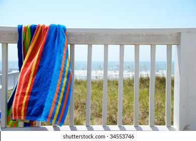 A colorful towel hanging on the porch at the beach house