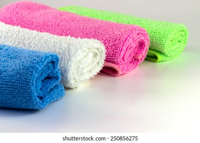 Colorful towels in rolls on a white background