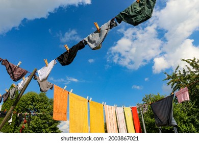 colorful towels and underwear hung to dry on clothesline with pegs