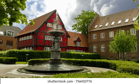 Colorful townhouse with an old fountain in the foreground, Aalborg, Denmark