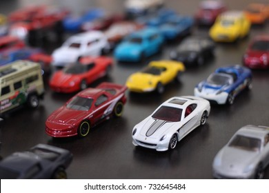 colorful toy car collection on wooden table in natural light. selective focus