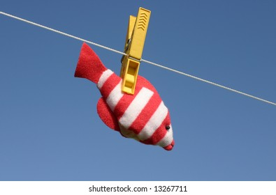 Colorful toy fish hanging on the laundry wire against blue sky