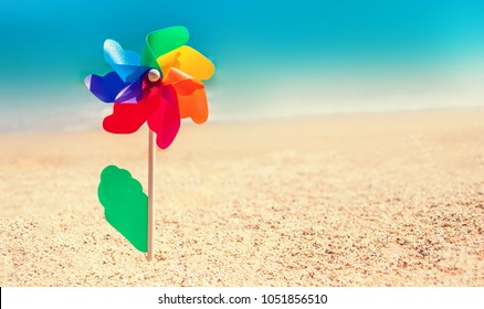 Colorful toy flower as a gay symbol and blurry sea beach background. Happy freedom summer concept
