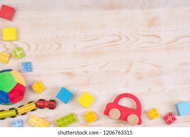 Colorful toys on white wooden background, top view with copy space