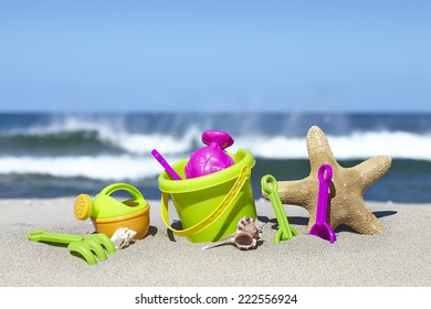 Colorful toys for sandboxes against the sea and the beach.