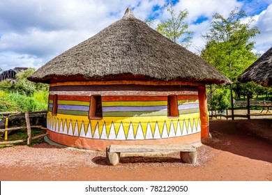 An colorful traditional african hut with walls built covered with mud and dung and roof thatched with a species of grasses