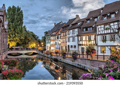 Colorful traditional french houses on the side of river Lauch at the evening in Colmar, France