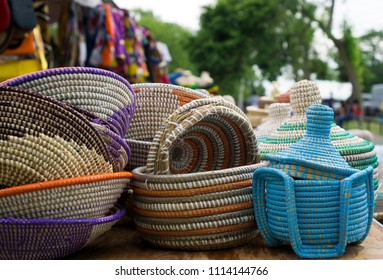 Colorful traditional woven baskets and ethnic clothes displayed for sale at an African outdoor festival.