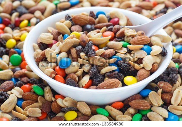 Colorful trail mix in a white bowl with spoon