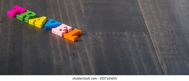 Colorful TRAVEL text on wooden table top