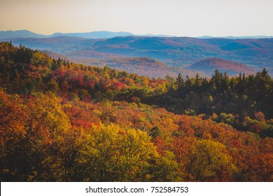 Colorful trees covering the mountains and rolling hills on a sunny day in autumn from the summit of Mont Tremblant, Quebec, Canada