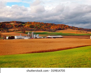 Colorful trees, turned orange, red, and yellow in October, stand behind and amongst the rolling hills of a farm in the countryside.