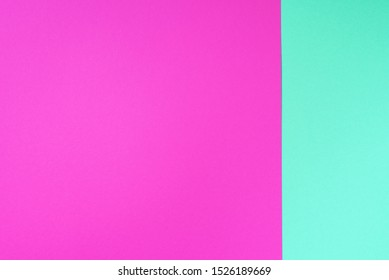 Colorful trendy green and pink paper background. Top view. Copy space.