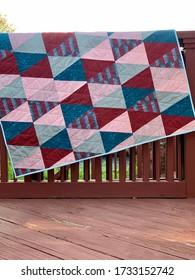 Colorful triangle quilt in blues and pinks set over a fence outdoors.