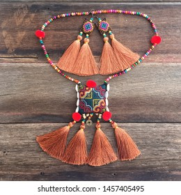 Colorful tribal fashion handmade embroidery accessories set earring and necklace made with woven thread and wooden beads on old wood texture background
