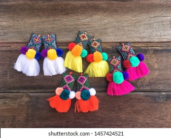Colorful tribal fashion handmade embroidery earring made with fabric woven thread and cotton ball on wooden texture background