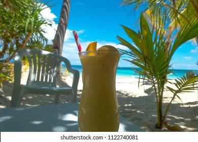 Colorful tropical beach scene with mango shake and straw - Malapascua, Cebu - Philippines