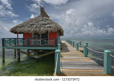 Colorful tropical bungalow with thatched roof on a wooden Caribbean pier in Belize