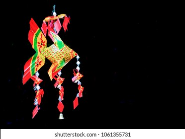 Colorful of tropical fish mobile hanging on black background,Thai-style fish mobiles (Pla ta pain),Plaited palm leaves and hand painted fish mobile,Weave fish from banana leaf,Mobile toy for baby,