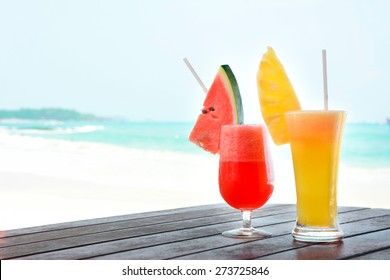 Colorful tropical fruit smoothies on the table at the beach - soft focus