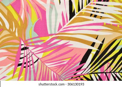 Colorful tropical leaves pattern on fabric. Pink, yellow, black and white palm leaves print as background.