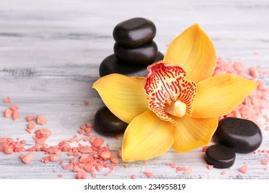 Colorful tropical orchid flowers and spa stones on color wooden background