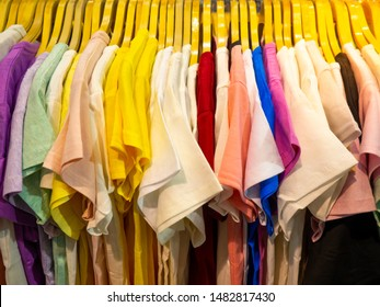 Colorful T-shirts are hanging in a clothes rail for sale in the flea market, Colorful T-shirts hanging on the rail.